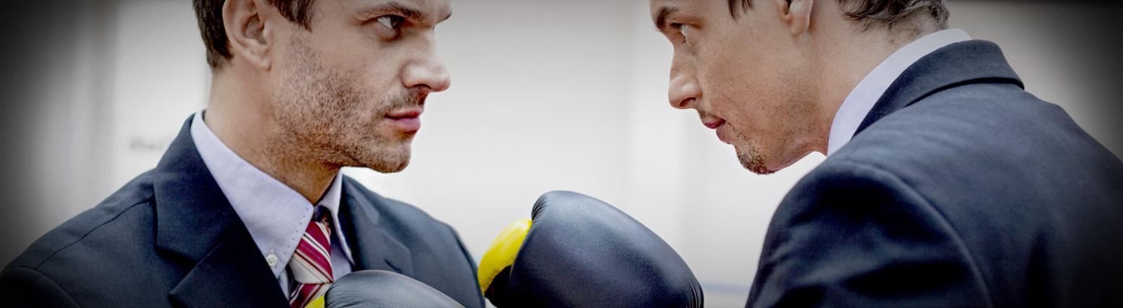 Machtkampf - zwei Männer stehen sich mit Boxhandschuhen gegenüber