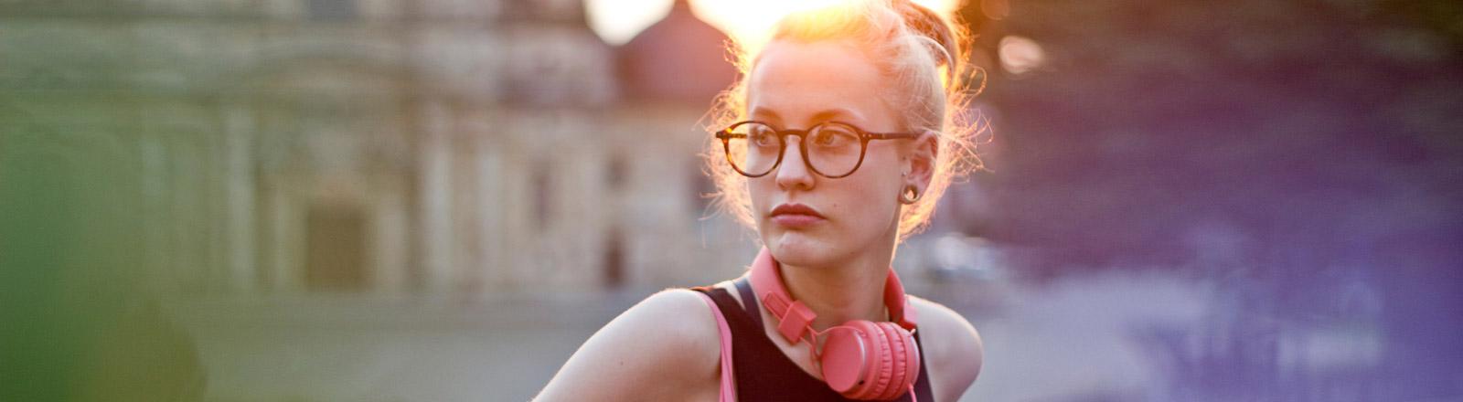Eine Frau mit Kopfhörern sitzt vor einer Kirche