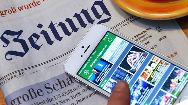 Auf einer Berliner Zeitung liegt ein Handy mit der digitalen Ausgabe.