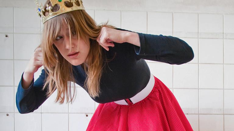 Eine Frau mit Krone auf dem Kopf hält sich die Ohren zu. Ihr Oberkörper ist leicht nach vorne gebeugt.