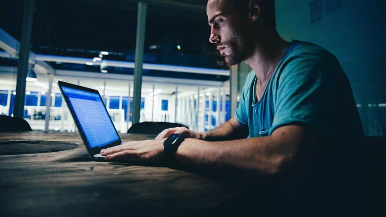 Mann sitzt mit Laptop am Tisch.