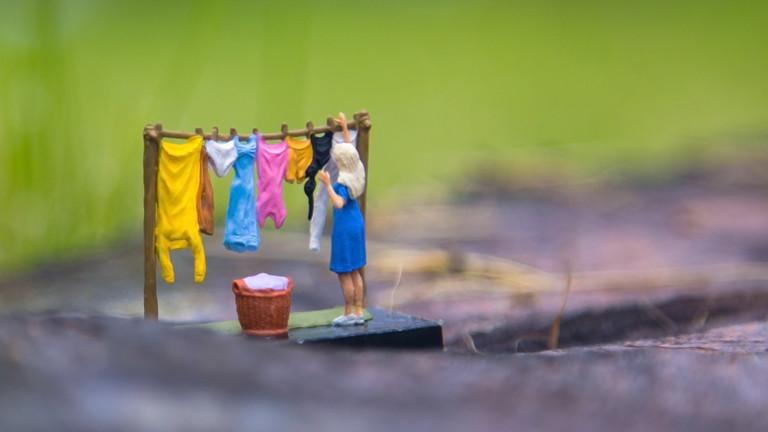 Miniatur-Hausfrau hängt Wäsche auf