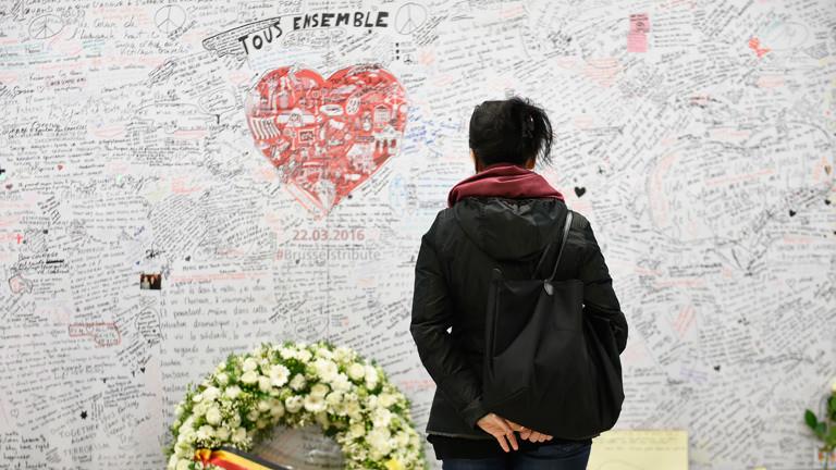 Eine Frau steht in der U-Bahn-Station Maelbeek in Brüssel vor einer Gedenktafel für die Opfer der Terroranschläge vom 22.03.2016