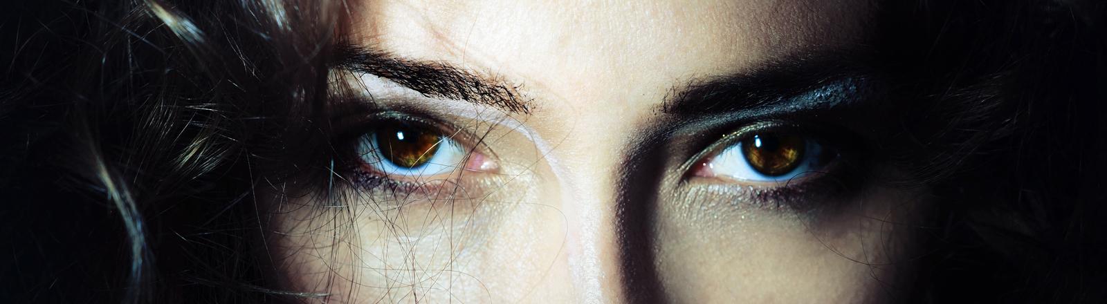 Nahaufnahme eines Frauengesichts mit dunklen Augen.