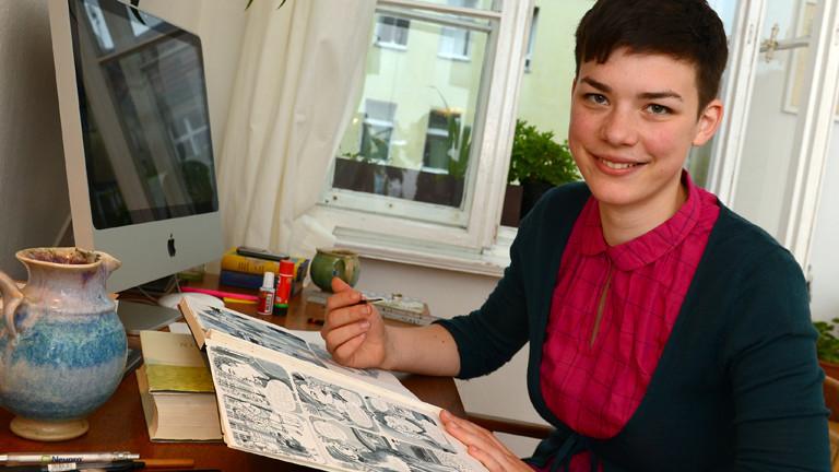 Paula Bulling an ihrem Schreibtisch mit einem Pinsel in der Hand.