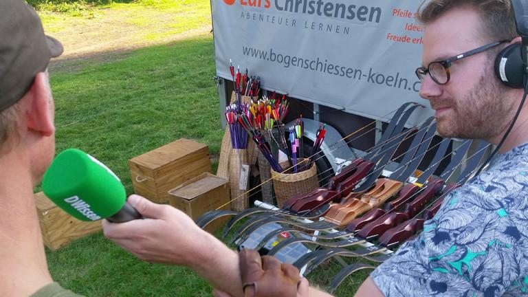 Christian Schmitt hält ein Mikrofon in der Hand. Im Hintergrund liegen viele Bögen und in Behältern sind viele Pfeile.