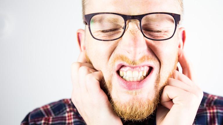 Ein Mann hält sich die Ohren zu und die Augen fest geschlossen