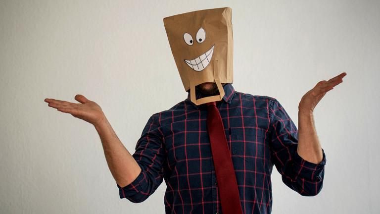 Ein Mann mit einer Tüte auf dem Kopf, auf der eine Grimasse gezeichnet ist.