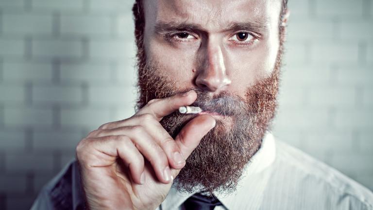 Ein Mann raucht mit ernstem Blick
