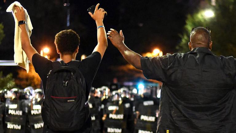 Protestler heben vor der Polizei in Charlotte, North Carolina die Hände