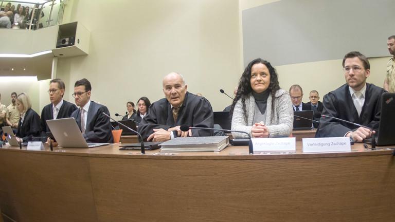 Die Angeklagte Beate Zschäpe (M) nimmt am 24.01.2017 im Gerichtssaal im Oberlandesgericht in München (Bayern) den Platz zwischen ihren Anwälten Hermann Borchert (l) und Mathias Grasel (r) ein. Links sitzen ihre drei weiteren Anwälte Anja Sturm (erste Reihe l-r), Wolfgang Heer und Wolfgang Stahl.