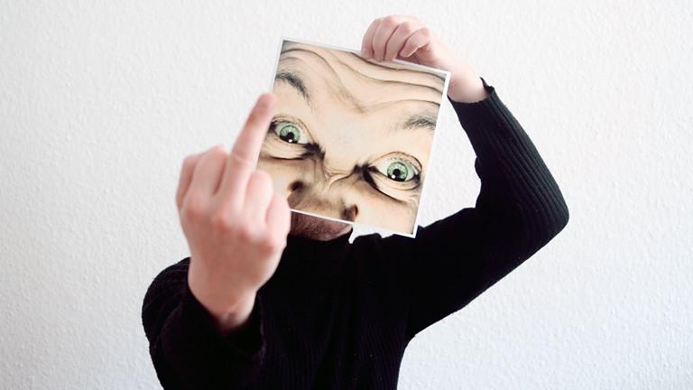 Mann zeigt Mittelfinger