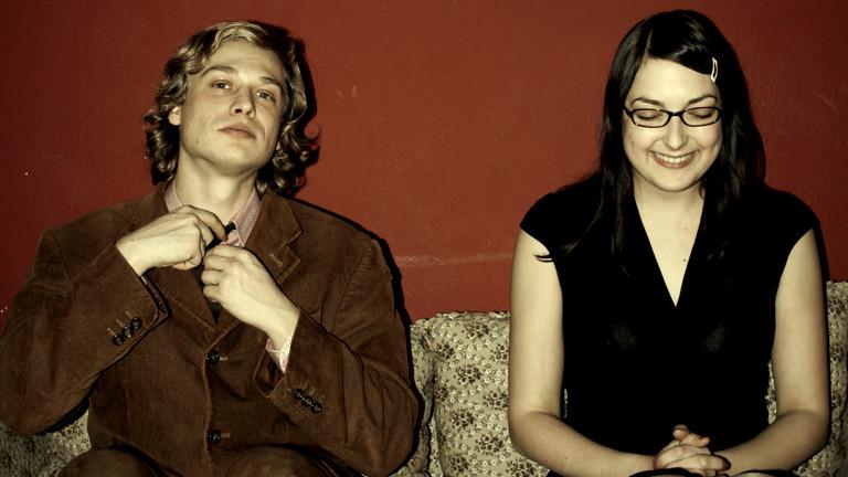 Ein junger Mann und eine junge Frau sitzen auf einem Sofa und lachen