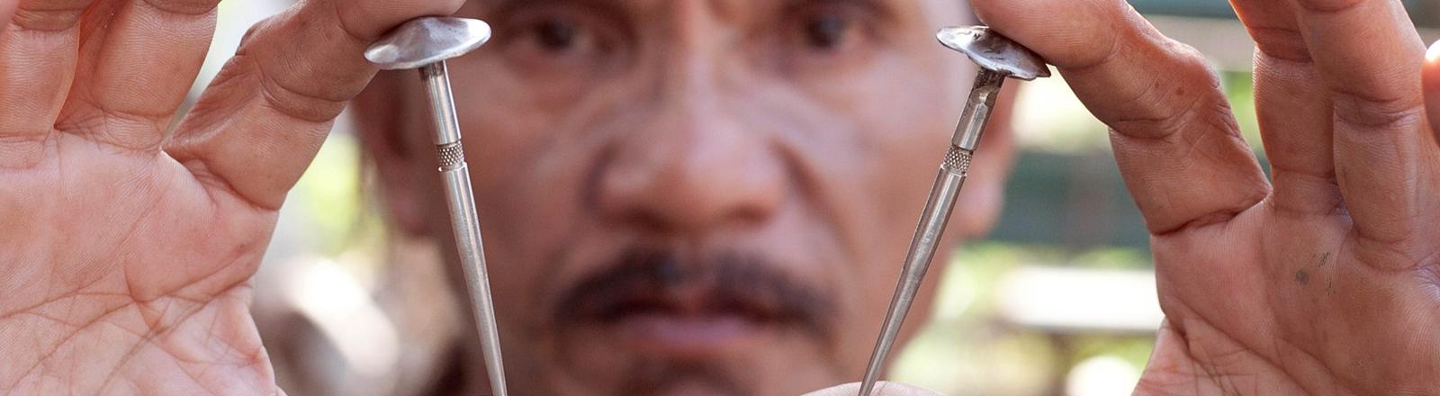 Ein Mann hält zwei Nägel in die Kamera zur Kreuzigung