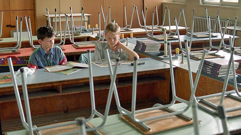 Zwei Jungs sitzen in einem Klassenraum und lesen.