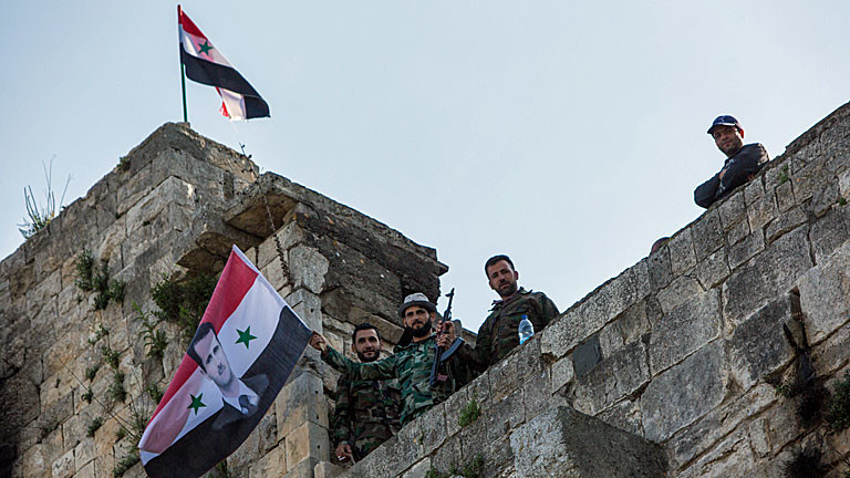 Regimetreue Soldaten schwenken auf der syrischen Festung