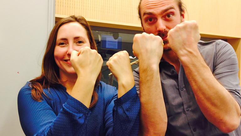 Tina Kießling und Till Haase stehen nebeneinander. Sie halten ihre Handgelenke in die Höhe. Zu sehen: keine Uhren.