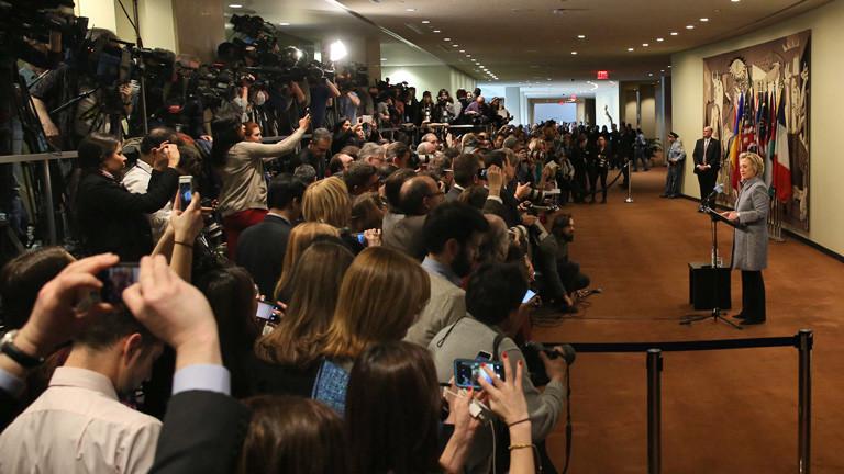Hillary Clinton steht vor einer großen Runde von Journalisten und redet; Bild: dpa