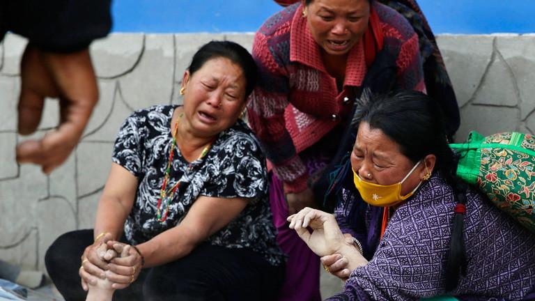 Drei Frauen halten Hände die Hände eines Toten. Sie weinen und trauern nach dem Erdbeben in Nepal; Bild: dpa