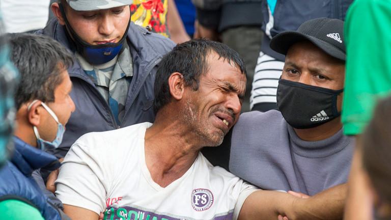 Ein Mann weint, er ist umgeben von Helfern. Nach dem Erdbeben in Nepal; Bild: dpa