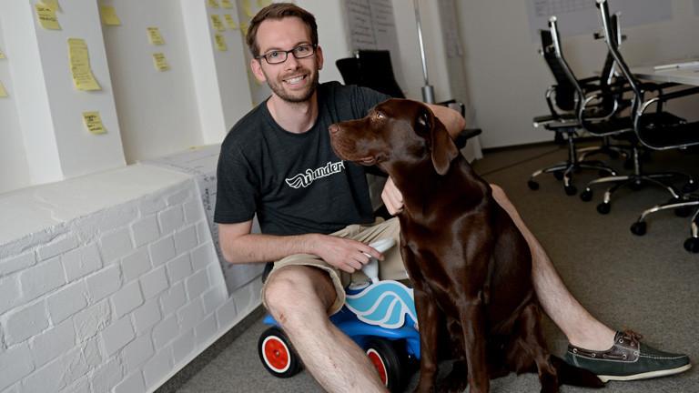 Gunnar Froh, Geschäftsführer der Firma Wundercar, sitzt in einem Büro auf einem Bobby-Car, ein brauner Hund sitzt neben ihm; Bild: dpa