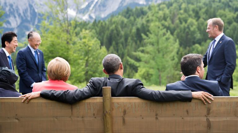 Auf einer Bank sitzen US-Präsident Barack Obama (Mitte), Angela Merkel (links) und Italiens Ministerpräsident Matteo Renzi (rechts). Das Bild zeigt die drei von hinten, am 08.06.2015 beim G7-Gipfel; Bild: dpa