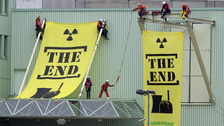 """Greenpeace-Aktivisten hängen gelbe Banner mit dem Schriftzug """"The End"""" an die Reaktoren des Atomkraftwerks Beznau."""