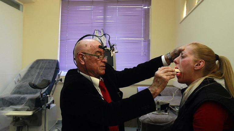 Ein Hals-Nasen-Ohren-Arzt untersucht in der Sozialen Poliklinik Elliniko eine Patientin