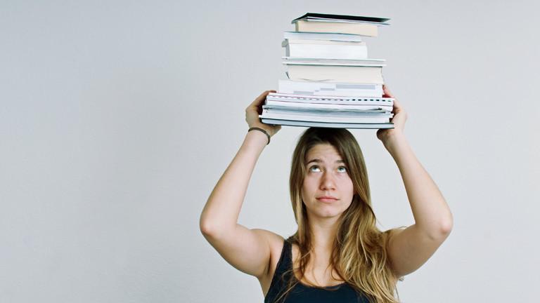 Eine junge Frau trägt Bücher und Unterlagen auf dem Kopf.