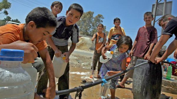 Jugendliche im Gazastreifen füllen Wasser ab