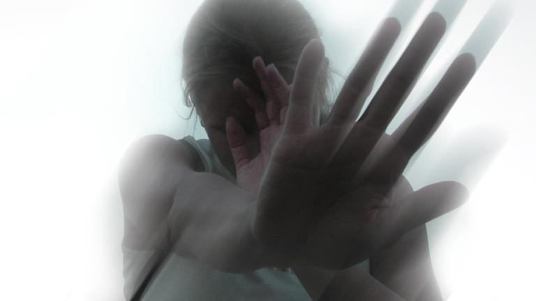 Eine Frau hält abwehrend die Hand vors Geschicht.