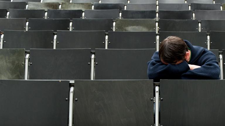 Ein Student sitzt einsam und müde im Hörsaal.
