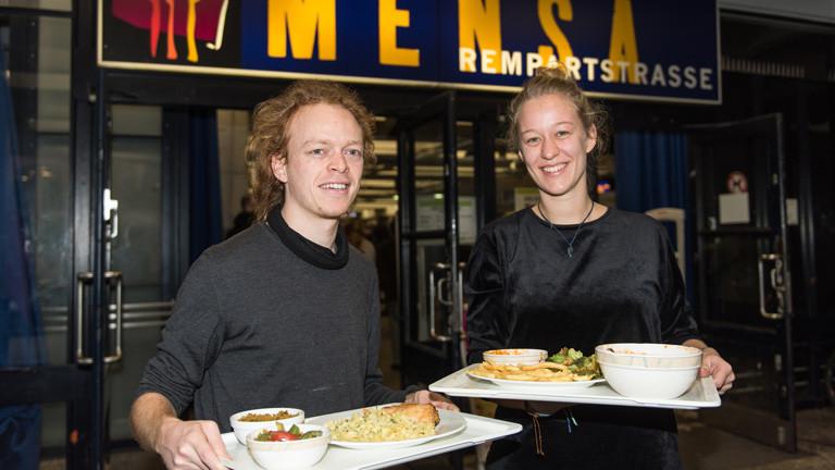 Jonathan Frey und Carlotta Krone halten am 24.11.2016 in Freiburg (Baden-Württemberg) Tabletts mit Essen. Das Essen hatten andere Studenten in der Mensa nicht aufgegessen und es auf die Abstellbänder gestellt. Die Mensa will jetzt eine Abdeckung bauen, um das sogenannte «Bändern» zu verhindern.