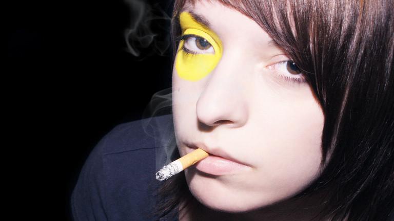 Eine Junge Frau mit Zigarette im Mundwinkel.