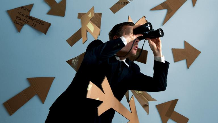 Ein Mann schaut durch ein Fernglas und ist umgeben von Pfeilen, die in verschiedene Richtungen zeigen