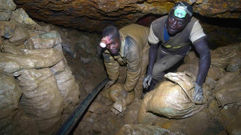 Aus einer Mine im Kongo schleppen zwei Männer Säcke. Sie tragen Alltagskleidung und haben Stirnlampen auf dem Kopf; Foto: dpa
