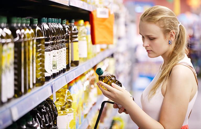 Eine Frau sucht Olivenöl im Supermarkt aus