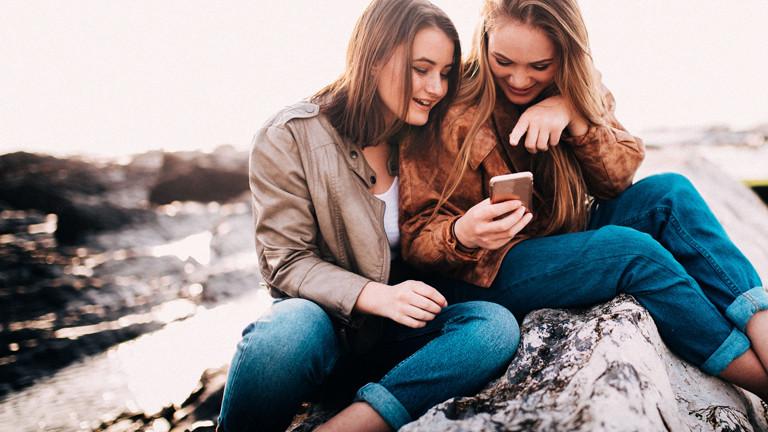 Zwei Mädchen schauen auf ihre Smartphones.