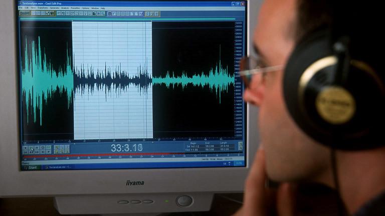 Ein Mann vor einem Monitor mit Audiospur