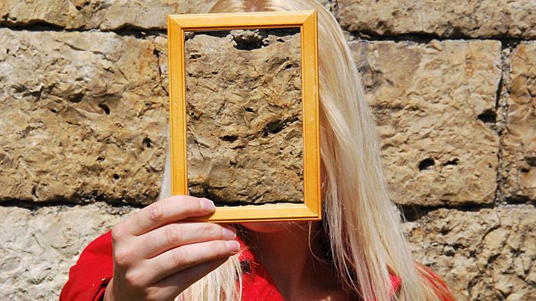 Blonde Frau im roten Kleid mit Bilderrahmen vor Gesicht, Gesicht verdeckt