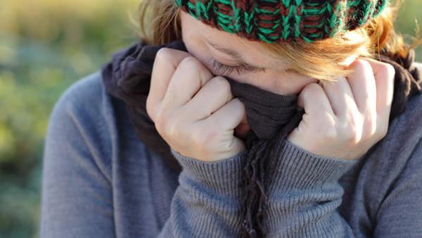 Eine Frau hat eine Erkältung oder Grippe. Sie fühlt sich krank und trägt Mütze und Schal.