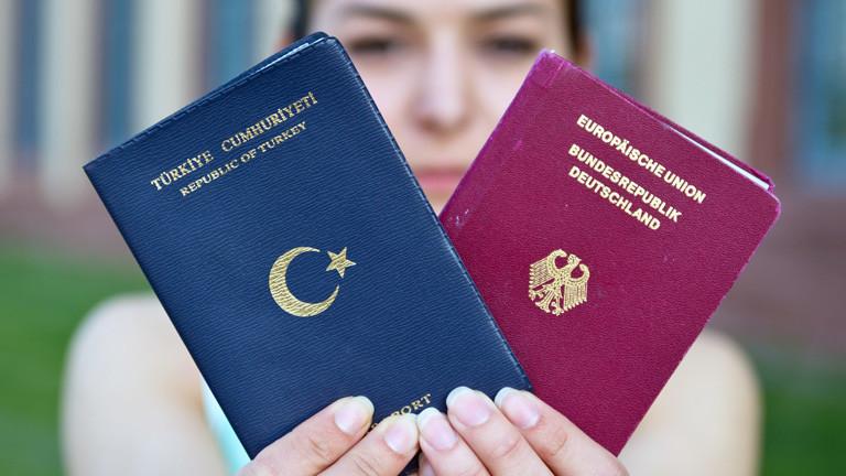 Eine Deutsch-Türkin hält ihre beiden Pässe hoch