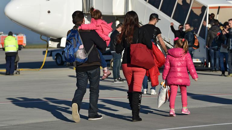 Abgelehnte Asylbewerber gehen zu ihrem Flieger
