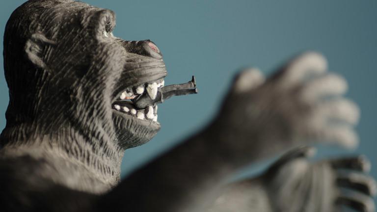 Affenfigur aus Plastik mit Männchen im Maul