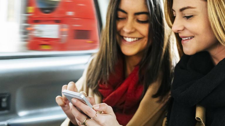 Zwei junge Frauen mit Smartphone im Taxi